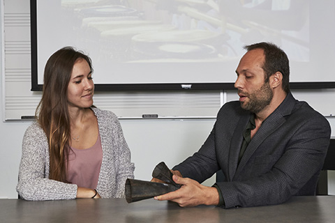 Professor and student examining a musical instrument