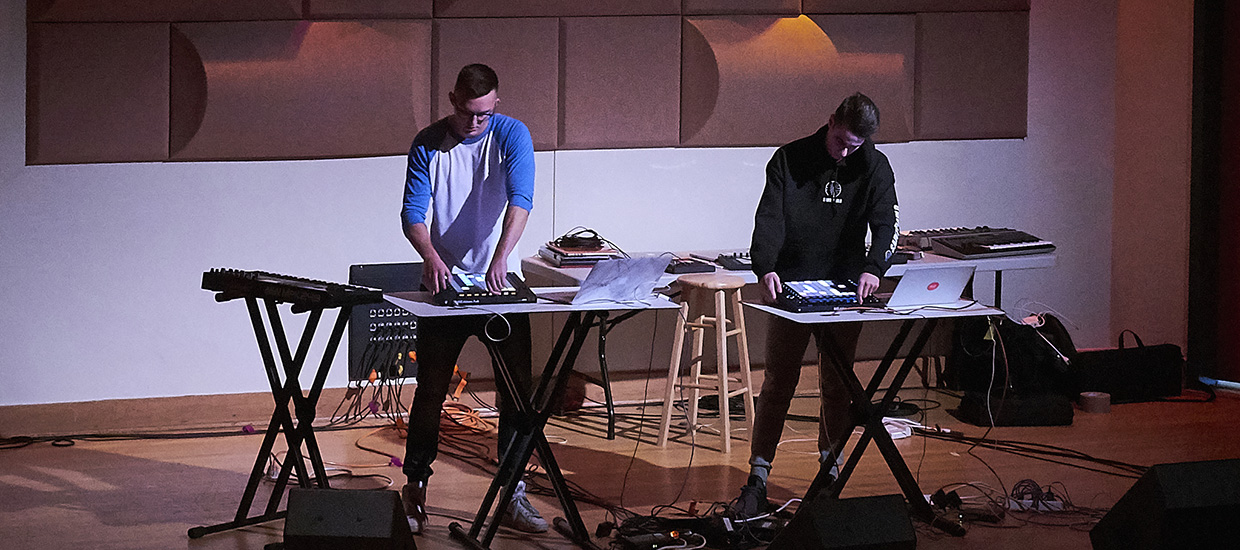 Duo performs live on stage with drum machiens